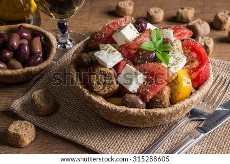 At the center the bread bowl of Greek salad on a table-napkin of burlap in the background olive oil, balsamic vinegar, glass of wine,olives, croutons.  Cretan Greek salad, lunch, snacks. Horizontal.   - stock photo