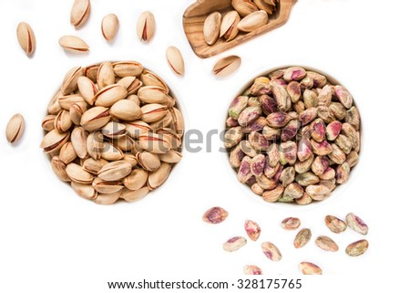 At the center 2 white bowls of pistachios right salted roasted pistachios and left raw pistachio kernels framed scattered pistachios on white background. 2 types of pistachios. Horizontal. Top view. - stock photo