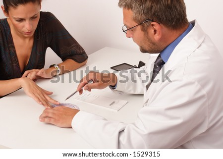 at the doctor's office - doctor explainig diagnosis to his female patient - stock photo