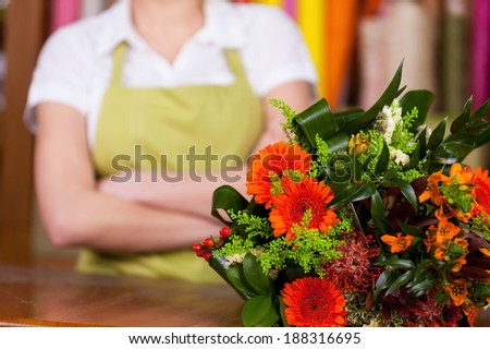At the flower shop. Cropped image of young blond hair woman in apron keeping arms crossed while bunch on flowers laying o foreground  - stock photo
