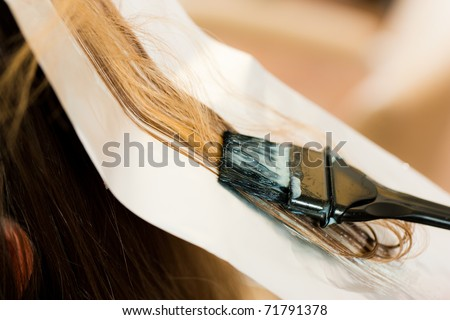 At the hairdresser � woman gets new hair colour; close-up on strand of hair - stock photo