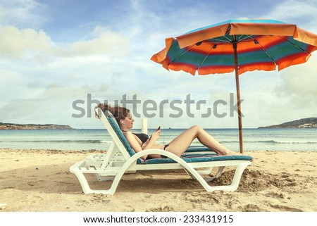 At the phone at the beach  - stock photo