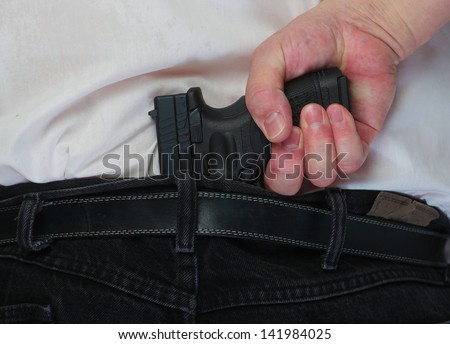 At the Ready/Man's hand clasped around automatic pistol tucked into his belt in the small of his back - stock photo