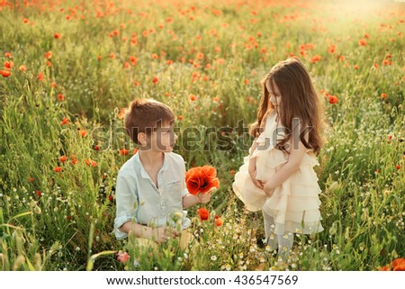 at the spring flower field little boy and girl collect red poppies - stock photo