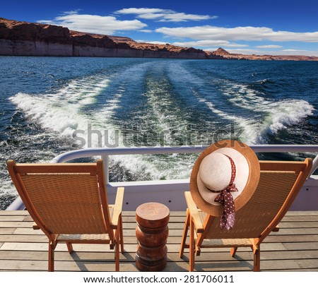 At the stern of the vessel are two deck chairs. On the back of one hanging elegant ladies straw hat. Waves from the boat cut through the Lake Powell on the Colorado River - stock photo