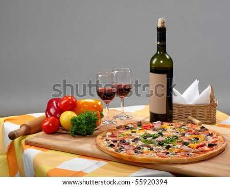 at the table, pizza, a bottle of wine, two glasses and a candle
