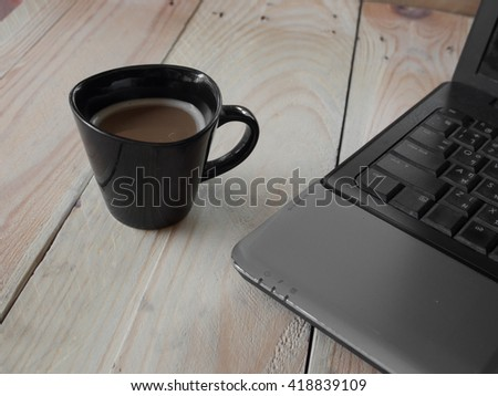 at the table with a cup of coffee and notebook computers