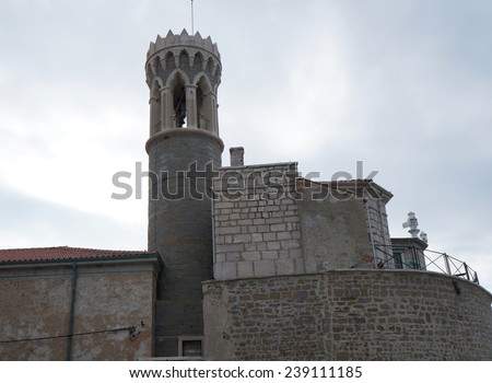 At the tip of the peninsula in Piran stands the Church of St. Clement and a lighthouse - stock photo