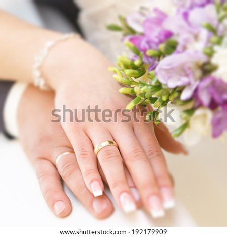 At the wedding, the bride and groom hand with gold rings. On the background of a bouquet of flowers. - stock photo