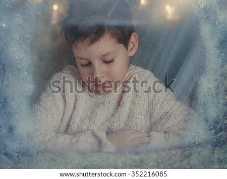 at the winter window frosty pattern on glass sits a boy in a knitted sweater