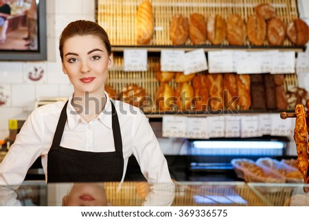 At your service. Attractive young woman working in a bakery looking to the camera smiling - stock photo