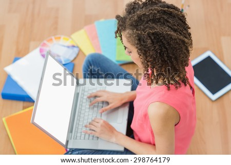 Atentive young creative businesswoman working on laptop - stock photo