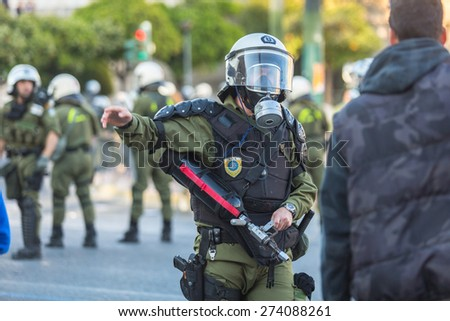 ATHENS, GREECE - APR 16, 2015: Riot police, take cover during a rally in front of the Athens University, which is under occupation by protesters leftist and anarchist groups. - stock photo