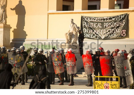 ATHENS, GREECE - APR 16, 2015: Riot police with their shield, take cover during a rally in front of Athens University, which is under occupation by protesters leftist and anarchist groups. - stock photo