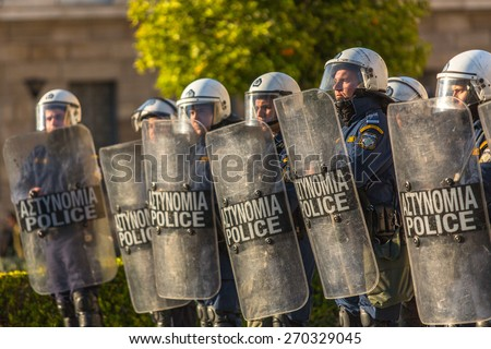 ATHENS, GREECE - APR 16, 2015: Riot police with their shields, take cover during a rally in front of the Athens University, which is under occupation by leftist protesters and anarchist groups. - stock photo