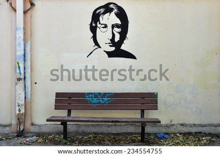 ATHENS, GREECE - AUGUST 30, 2014: Famous musician John Lennon from The Beatles portrait stencil graffiti on textured wall and wooden bench. - stock photo