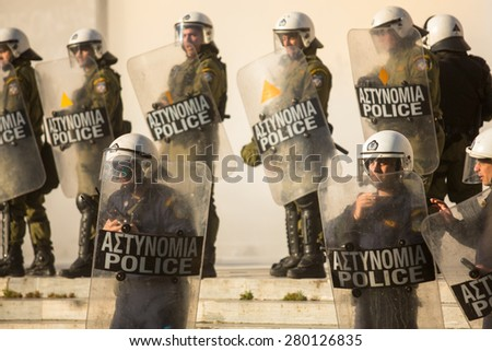 ATHENS, GREECE - CIRCA APR, 2015: Riot police with their shield, take cover during a rally in front of Athens University, which is under occupation by protesters leftist and anarchist groups. - stock photo