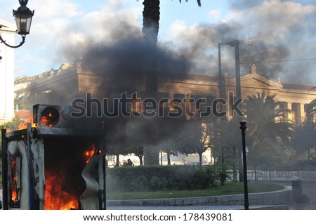 ATHENS-GREECE DEC. 09. Smoke from a burning booth, covers the historical building of National University of Athens, during demonstration in central Athens, December, 09, 2008. - stock photo
