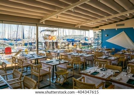 ATHENS, GREECE, DECEMBER 10, 2015: Modern restaurant interior with scenic seaside view - stock photo