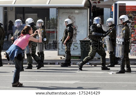 ATHENS, GREECE-FEB. 24 Girl photographing riot police, during demonstration, in central Athens, February 24, 2010.  - stock photo
