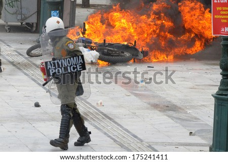 ATHENS, GREECE-FEB.23 Riot police looking at motorbike on fire, during demonstration in Syntagma square in Athens  February 23, 2011.     - stock photo