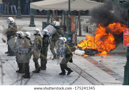 ATHENS, GREECE-FEB.23 Riot police next to motorbike on fire, during demonstration in Syntagma square in Athens  February 23, 2011.     - stock photo