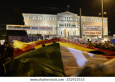 Athens, Greece, February 15, 2015. Protesters wave Greek, Italian and Spanish flags in front of the parliament during an anti-austerity and pro-government demonstration. - stock photo