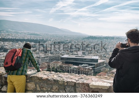 ATHENS, GREECE - JANUARY 31 2016: Visitors at the Acropolis take pictures of the Archaeological Museum of Athens - stock photo