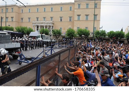 ATHENS, GREECE -JUNE 15. Angry crowd pushing police erected fence outside the Greek Parliament during demonstration, in Athens, June 15, 2011.  - stock photo