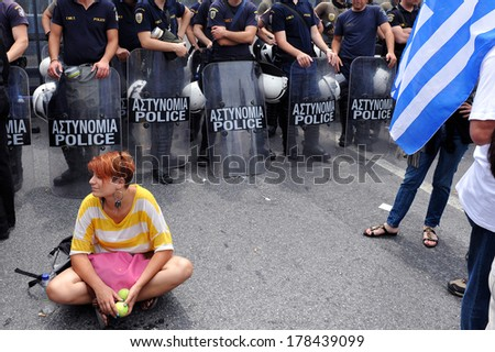 ATHENS-GREECE,JUNE 15. Greek economic crisis. A young girl is protesting peacefully in front of a riot police during demonstration in Athens, June 15, 2011.  - stock photo
