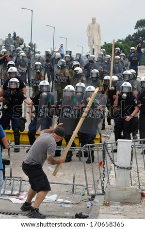 ATHENS, GREECE -JUNE 15. Man threatening riot police with stick at the Greek Parliament during demonstration , in Athens, June 15, 2011. - stock photo