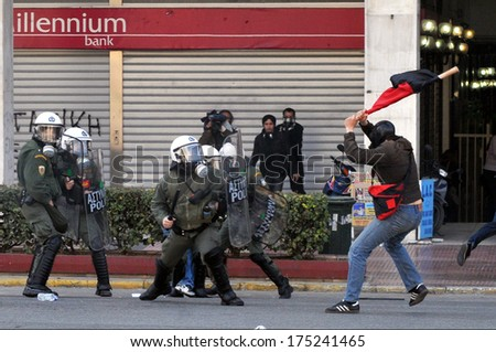 ATHENS, GREECE-March 11 Riot police under attack from rioter, during demonstration, in central Athens, March 11, 2010. - stock photo