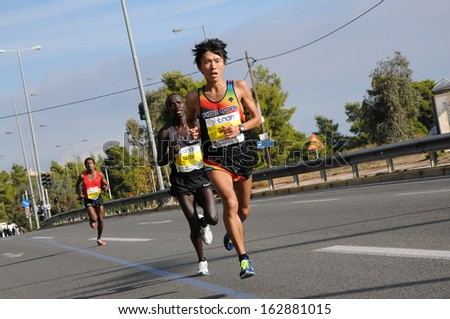 ATHENS, GREECE - NOV 10, 2013: 31st Athens Classic Marathon. The japanese runner, Inoue Takahiro (21), arrives at the 16th km and finishes seventh (2:20:10).  - stock photo