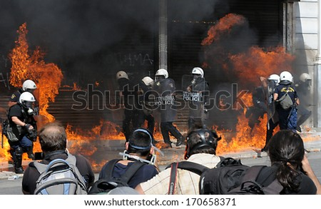 ATHENS, GREECE -SEPT. 26. Photojournalists taking shots of riot police in flames, from Molotov bombs during demonstration in Athens. September 26, 2012. - stock photo