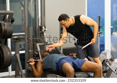 athlete african man in gym with personal fitness trainer - stock photo