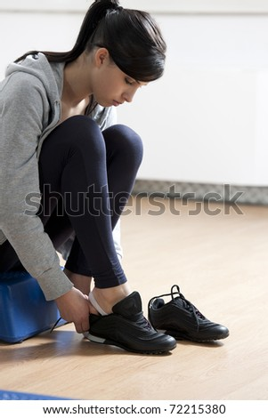 Athlete at health club, tying shoes. - stock photo