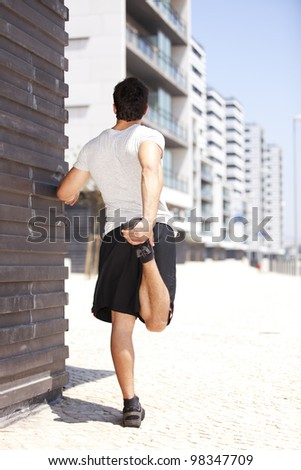 Athlete at the city warming and stretching - stock photo