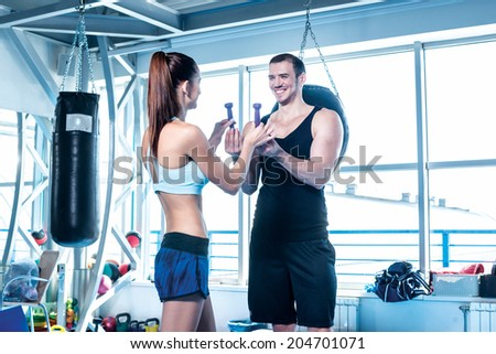 Athlete athlete handed small dumbbells. Young couple athletes men and athletes engaged in training with dumbbells and heavy weights. - stock photo