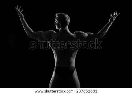 Athlete bodybuilder man demonstrating his perfect muscular body - muscles of the back and arms. Over black background.  - stock photo