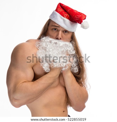 athlete bodybuilder shirtless with long hair posing with a beard and a cap of Santa Claus on a white background