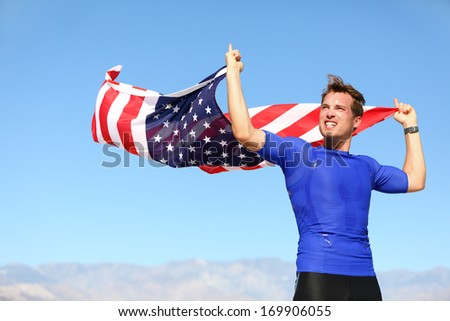 Athlete cheering holding US flag motivated athletic young man standing with the American flag raised in the air in his hands blowing in the breeze against a clear sunny blue sky - stock photo