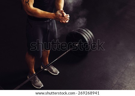 Athlete clapping hands with talc before deadlift barbells workout - stock photo
