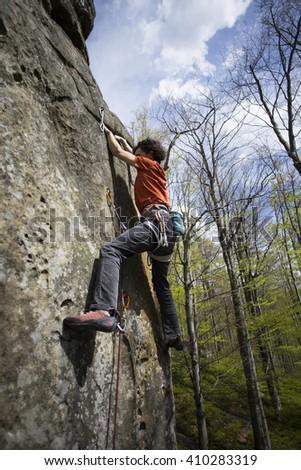 Athlete climbs on rock with rope. - stock photo