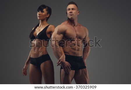 Athlete couple. Bodybuilder and his girlfriend in underwear posing over grey background. - stock photo