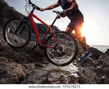 Athlete crossing rocky terrain with water barrier with his bicycle - stock photo