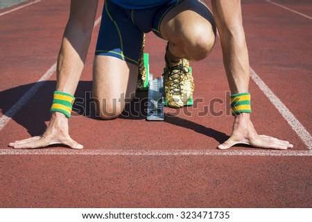 Athlete crouching at the starting line of a running track with gold shoe feet in sprinter starting blocks - stock photo