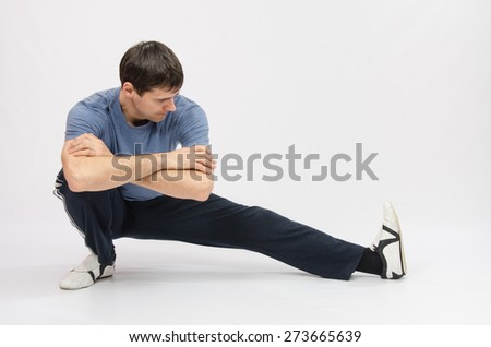 Athlete crouching stretches muscles of left leg