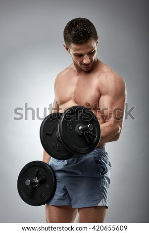 Athlete doing biceps curl with dumbbells, studio shot - stock photo