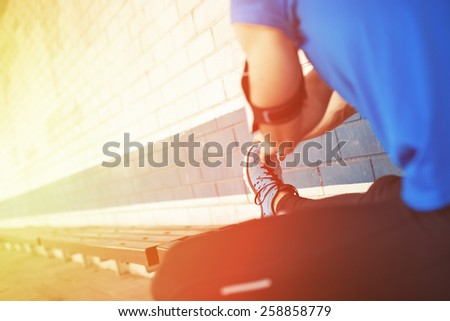 athlete doing preparation exercise (intentional sun glare) - stock photo