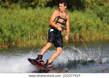 athlete enjoys skateboarding on the river and looking away - stock photo